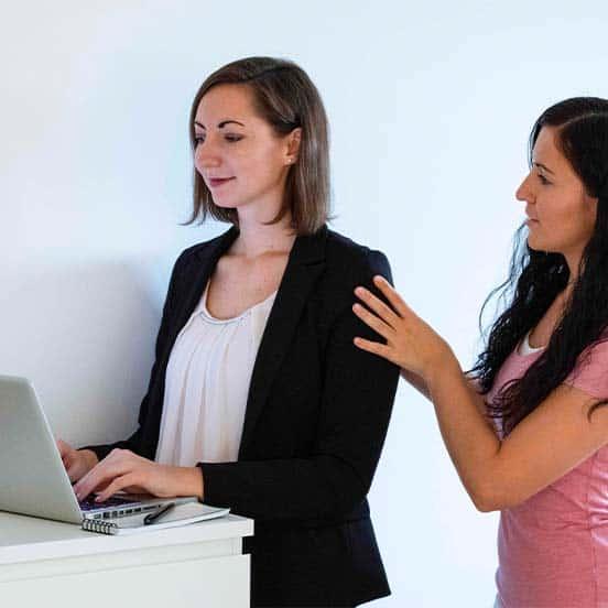 Physiotherapeutin Daniela führt bei einer Büroangestellten eine Ergonomie-Schulung am Steharbeitsplatz durch.
